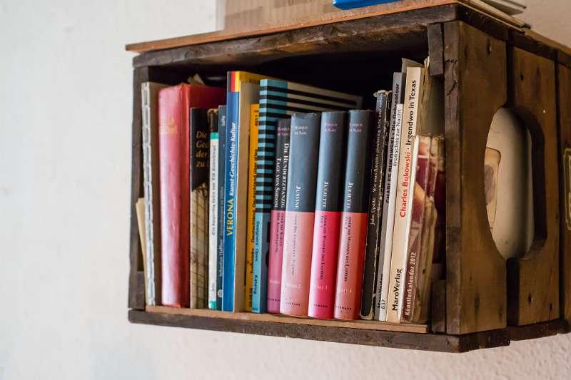 Eine umfunktionierte Bierkiste aus Holz dient als Bücherregal.