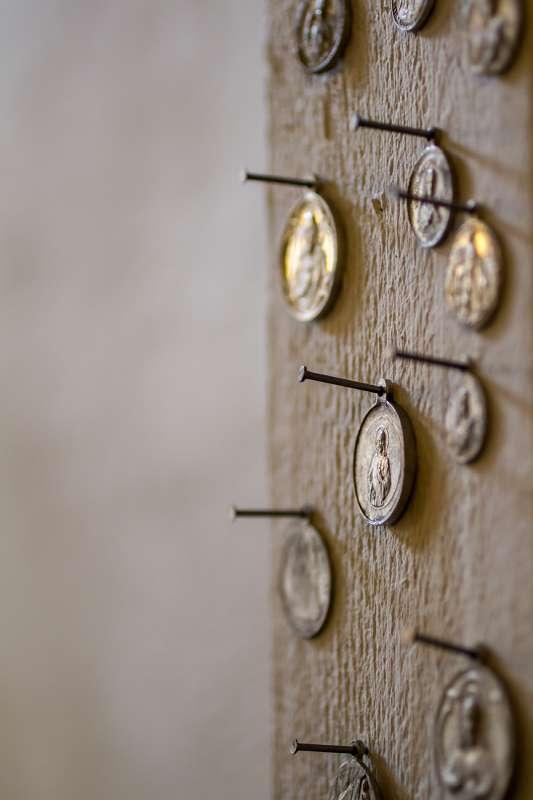 Münzen bzw. Heiligenbilder an eine Wand genagelt.