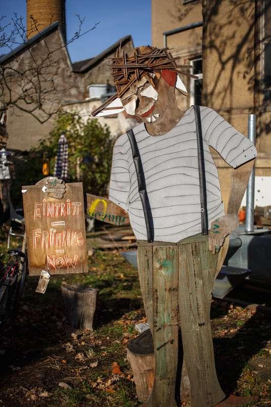 Eine Holzfigur begrüßt die Gäste am Hoftor.