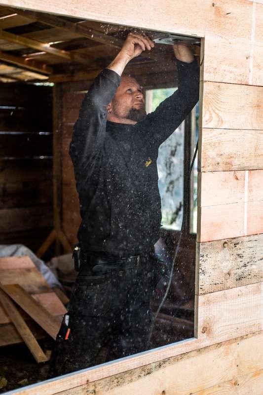 Ein Handwerker integriert ein Fenster in die Blockhütte.