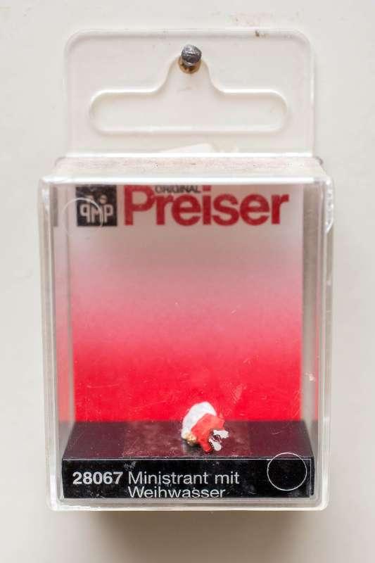 Detailaufnahme einer Preiser Miniaturfigur eines Ministranten mit Weihwasser.