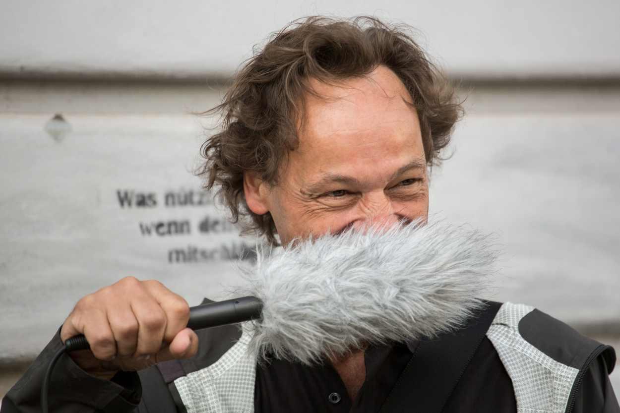 Bertram Weisshaar trägt das Aufnahmegerät als Schnurbart.