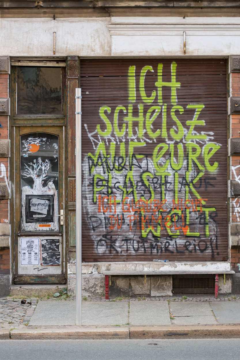 Auf dem heruntergelassenen Rolläden eines Geschäfts in der Merseburger Straße in Leipzig steht der Text, »Ich scheisse auf eure Plastikwelt«.