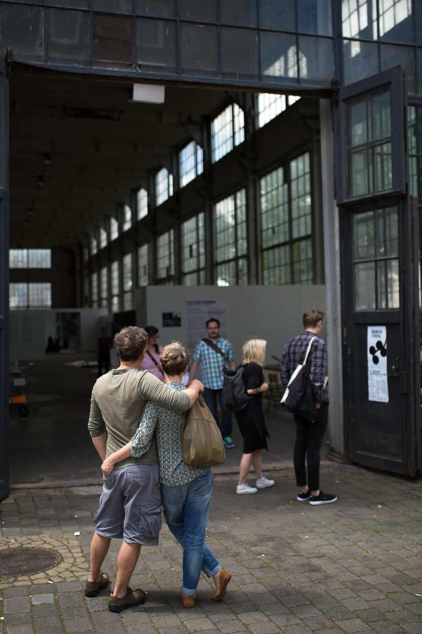 Ein Pärchen steht vor dem Eingang der großen Halle des Westwerks Leipzig.