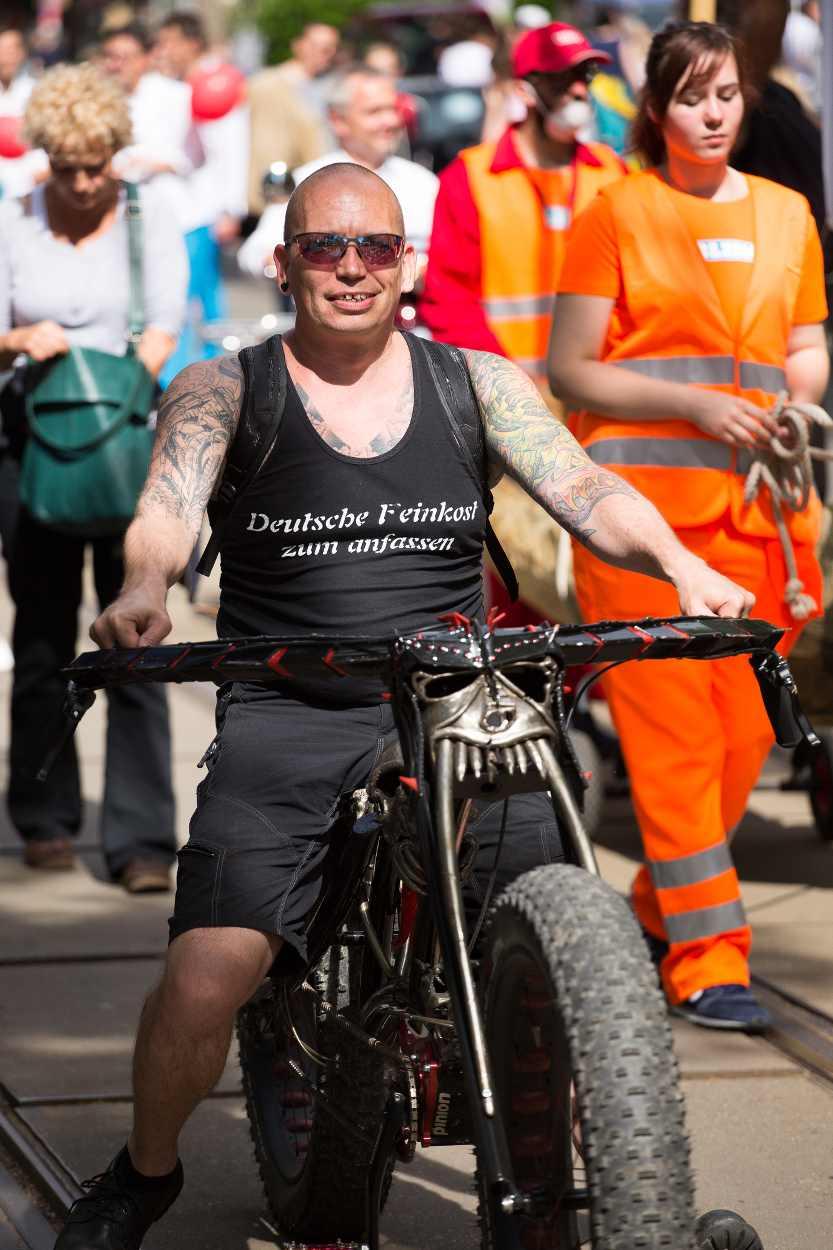 Deutsche Feinkost zum Anfassen – Ein Teilnehmer der Parade zeigt seinen Körper und sein Motorrad.