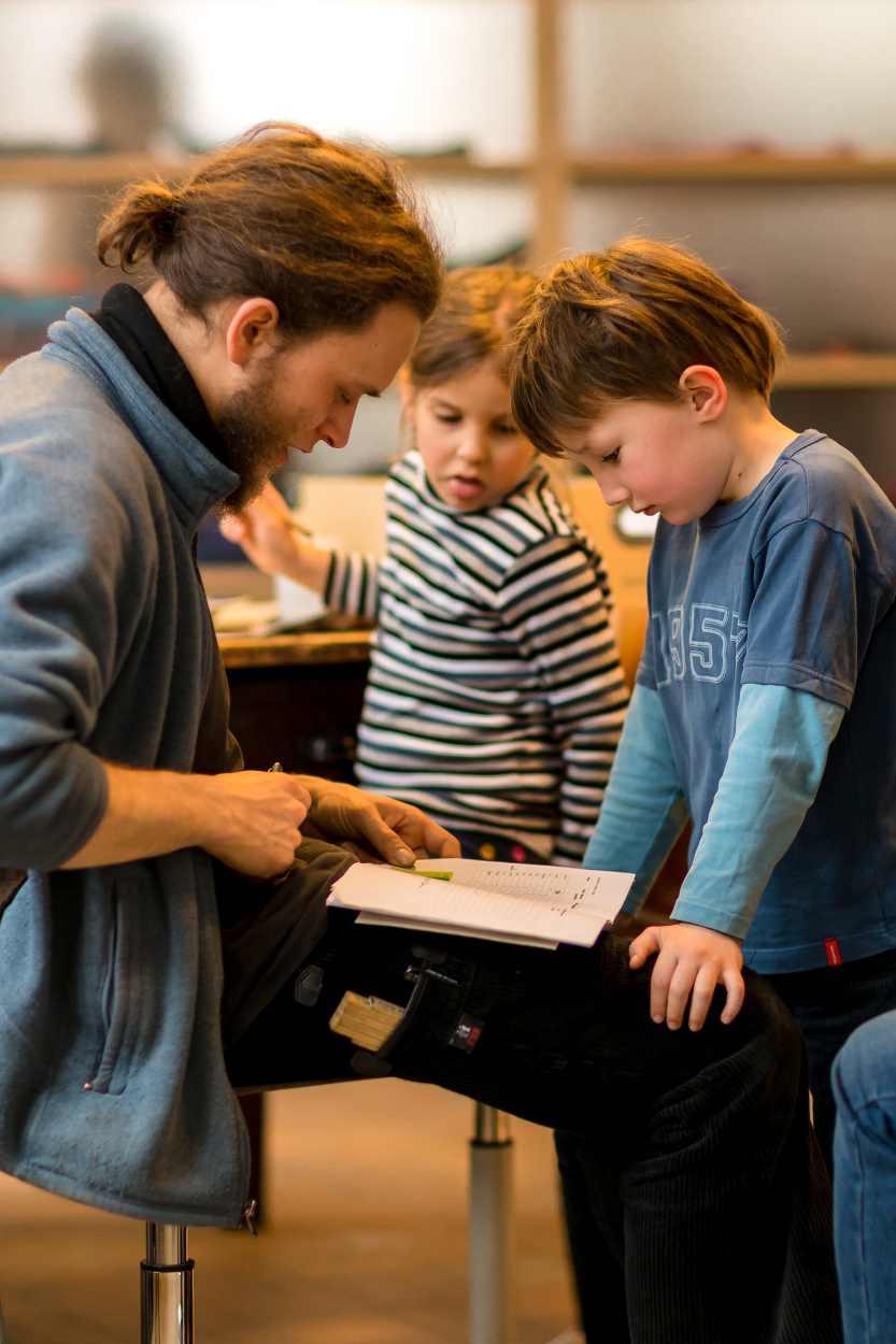 Buchkinder und Betreuer besprechen eine Geschichte.