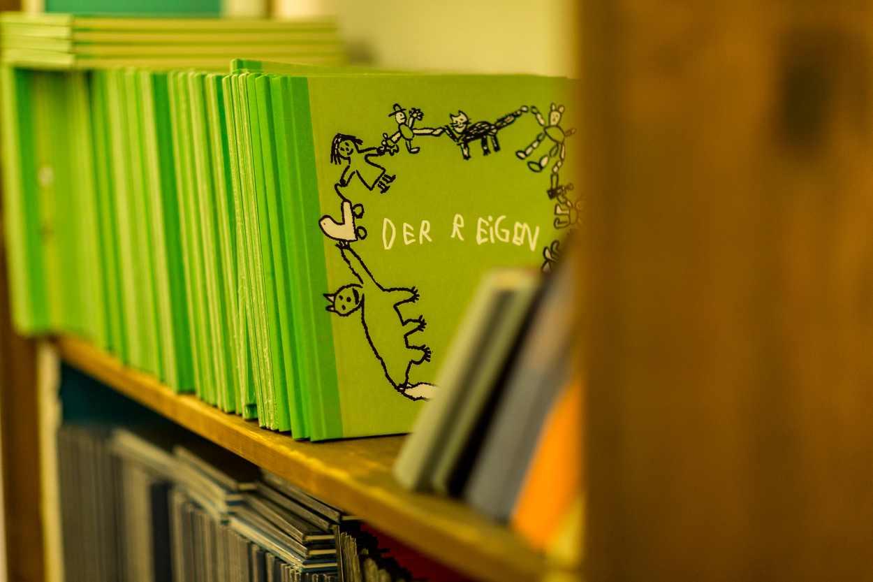 Mehrere Bücher stehen in einem Regal in der Werkstatt der Buchinder.