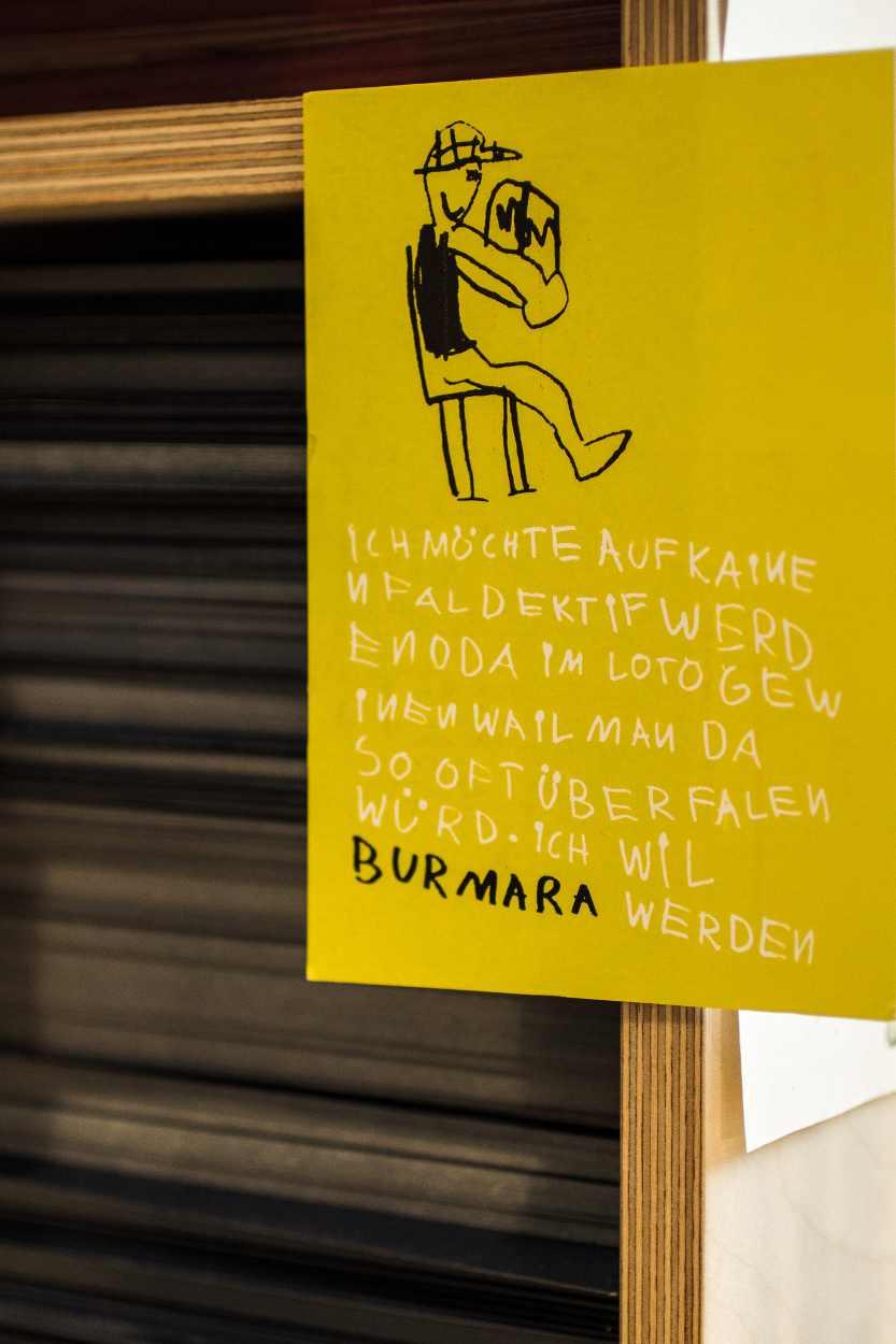 Postkarte an einem Regal der Buchkinder Leipzig.