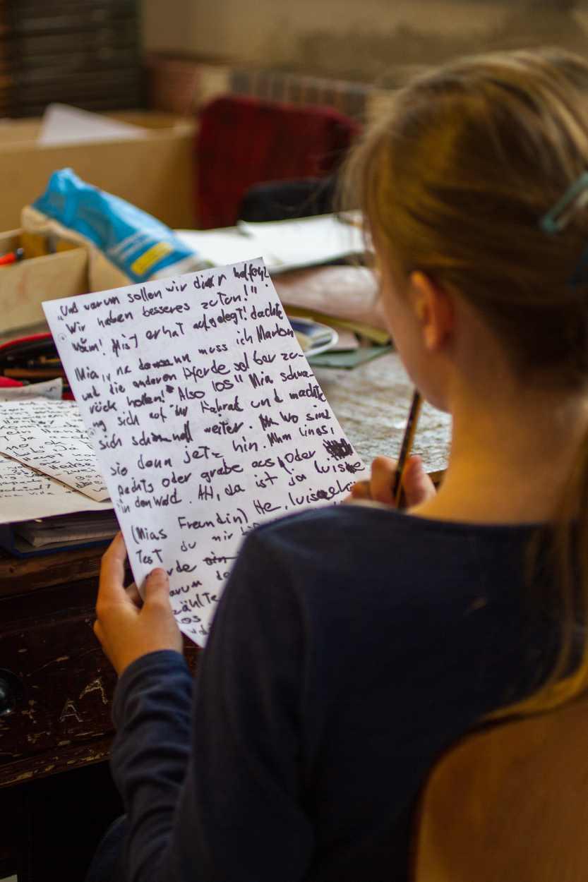 Ein Buchkind liesst ihren Textentwurf für eine Geschichte.