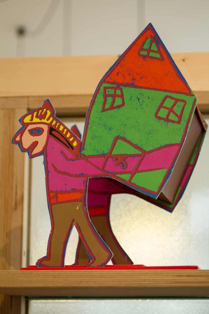 Detailaufnahme einer Figur, die ein Haus auf dem Rücken trägt.