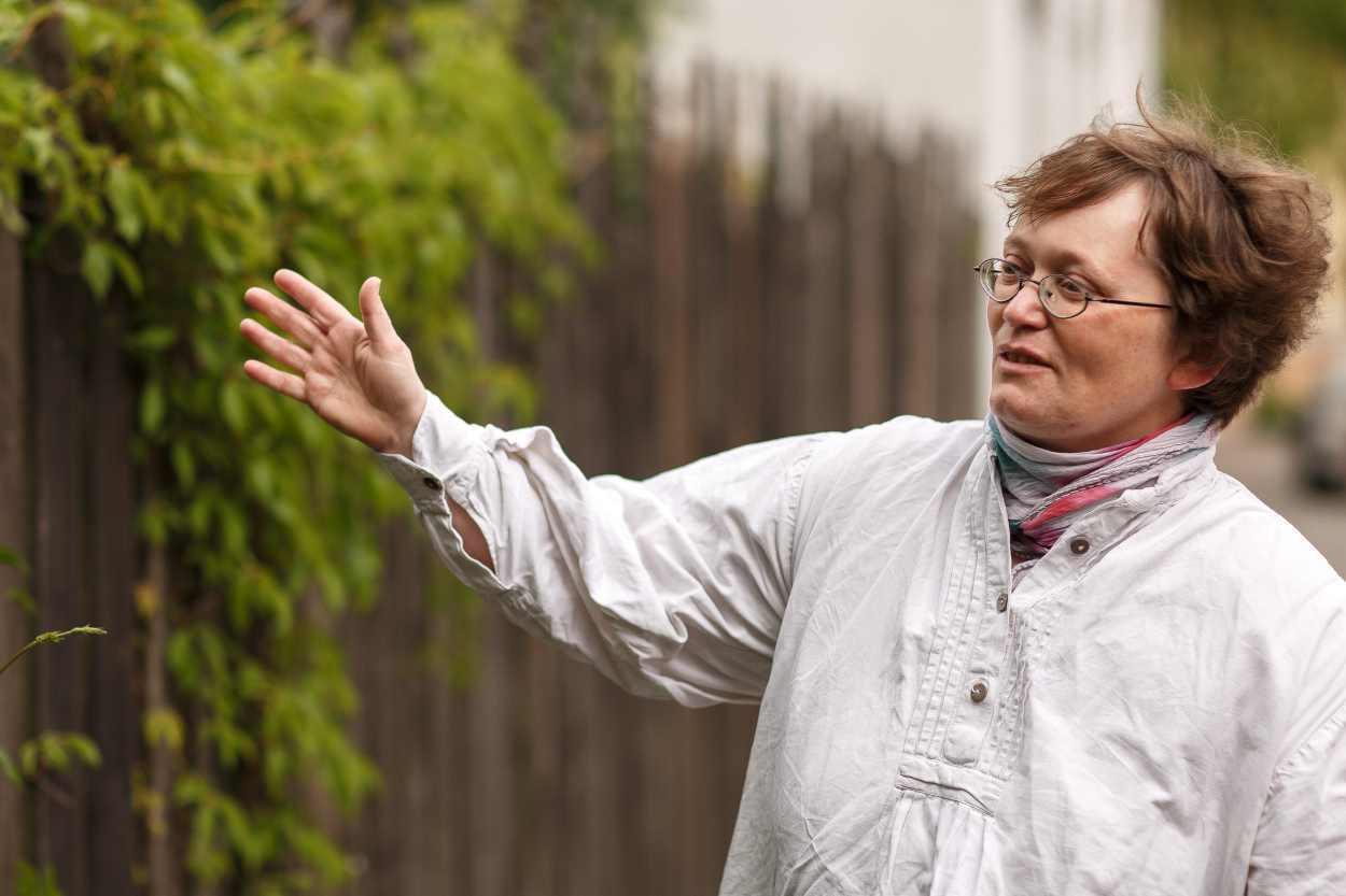 Christina Weiß vor dem Zaun des Hauses in Leipzig Lindenau in dem sie lebt.