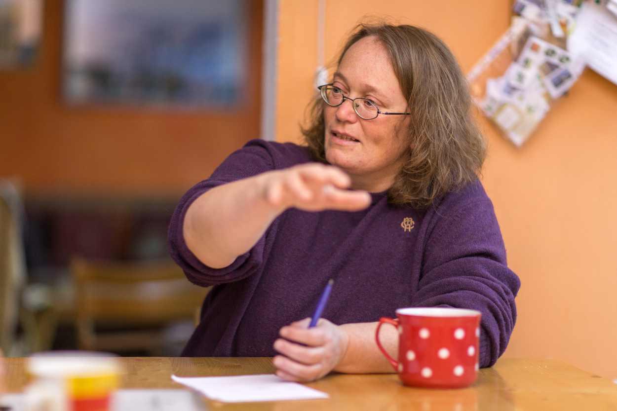 Christina Weiß sitzt an einem Tisch in ihrer Wohnung in der Roßmarktstraße.
