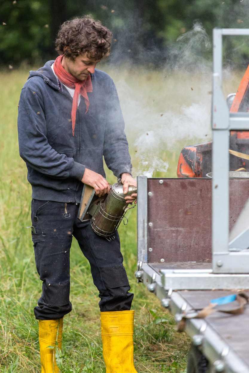 Christopher Mann räuchert die Bienenstöcke ein, um die Bienen zu beruhigen.