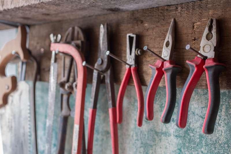 Verschiedene Werkzeuge hängen an einem Holzbrett im Atelier von Frank Schwärzel in Leipzig.