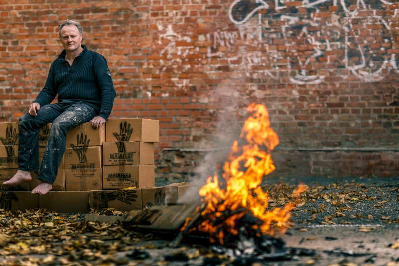 Helge Hommes beobachtet auf Stapeln seines Manifestes sitzend das gerade entzündete Feuer.