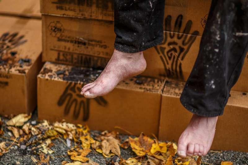 Verpackte Schachteln des Manifests im Hintergrund, während davor Helge Hommes Füße zu sehen sind.