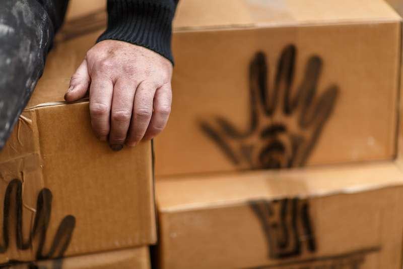Eine Hand – das Erkennungszeichen des Manifests – ist auf einem Karton zu sehen.