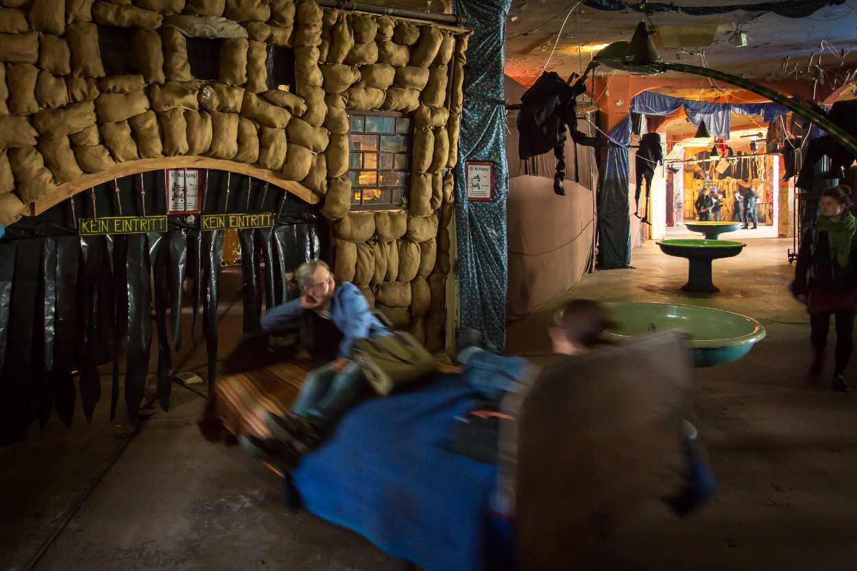 Zwei Gäste fahren auf einem der fahrenden Betten in die Unterwelt von Bimbotown.
