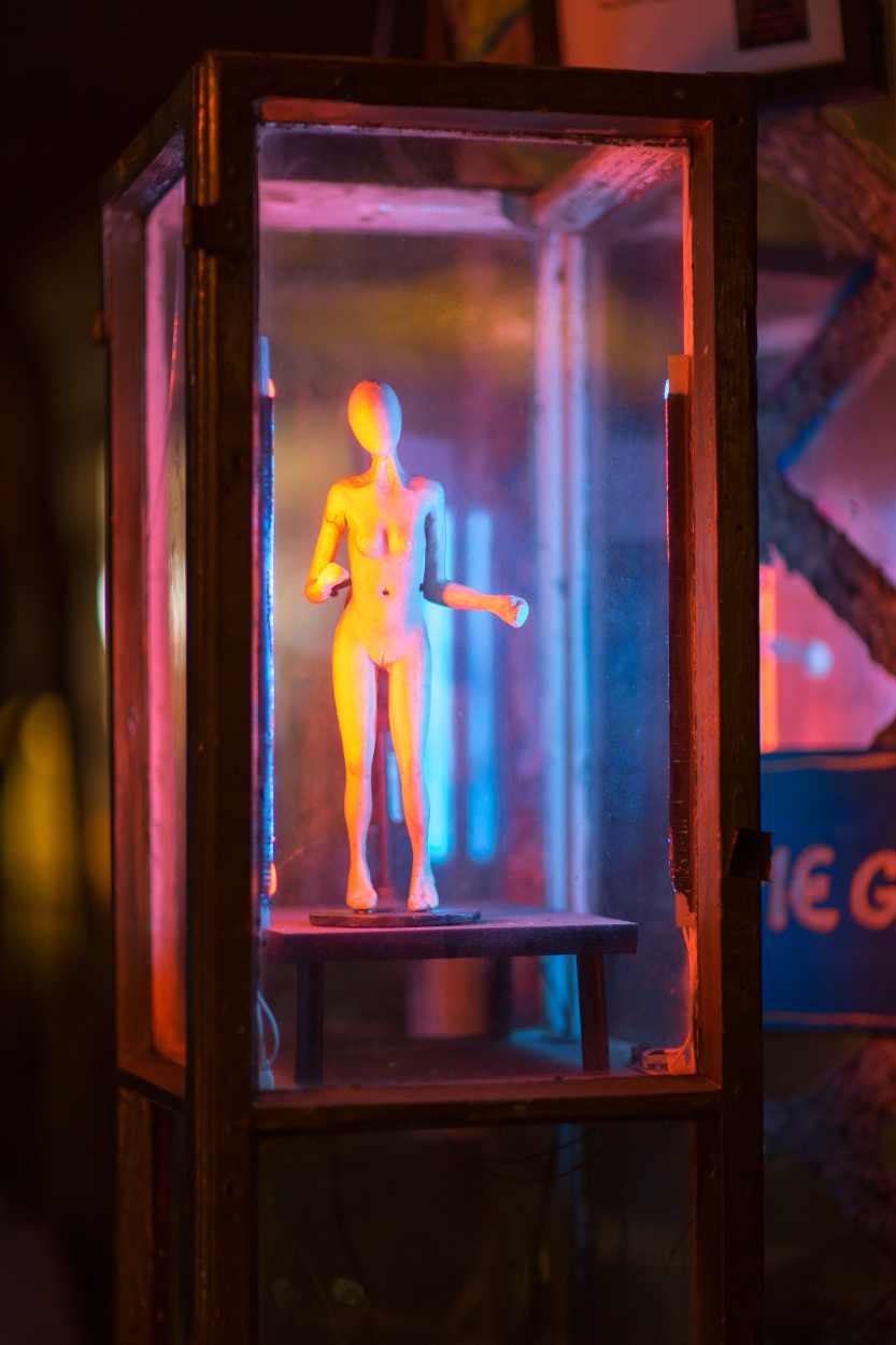 Eine kleine Figur in einem Glaskasten.