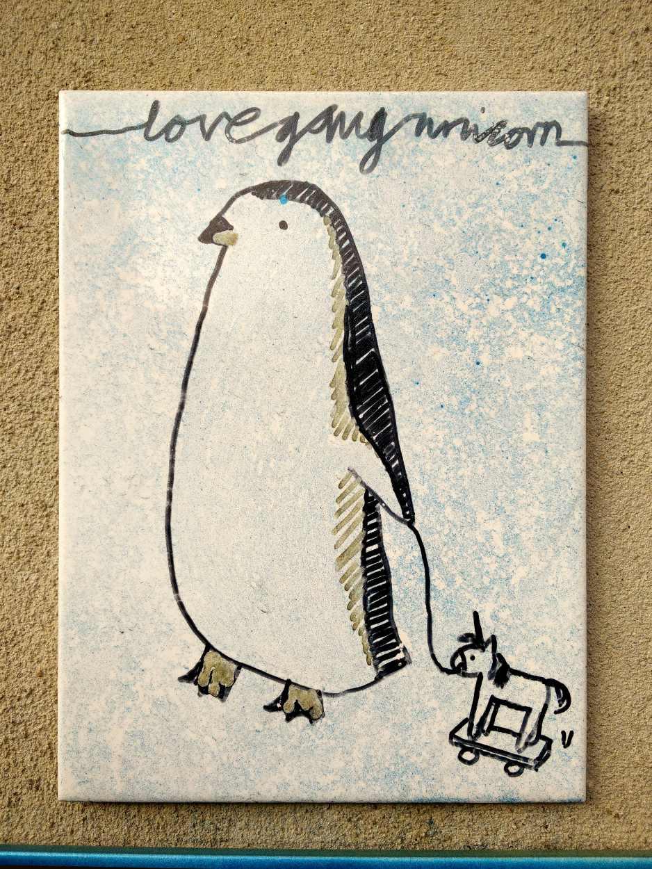 Mit einem Pinguin bemalte Kachel auf den Straßen von Leipzig Plagwitz, der ein Spielzeugschaukelpferd an einer Schnur hinte sich herzieht.