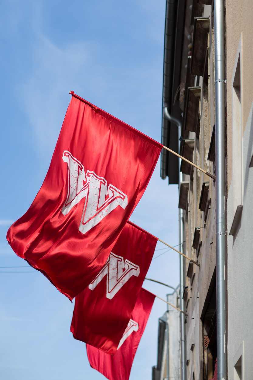 Fahnen kündigen die Veranstaltungen im Westflügel Leipzig an.