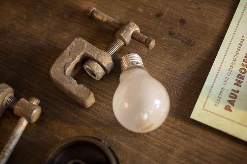 Eine Glühbirne liegt neben Schraubstöcken auf einem Tisch.