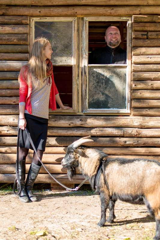 Christiane mit dem Ziegenbock vor der Blockhütte.